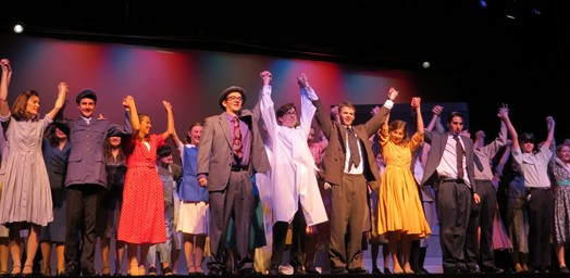 high school theater performers taking a final bow