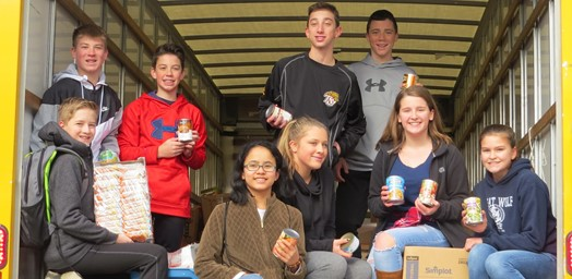 students loading food truck for food bank delivery
