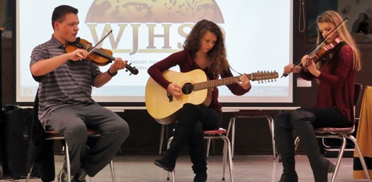 trio of performers on violin and guitar
