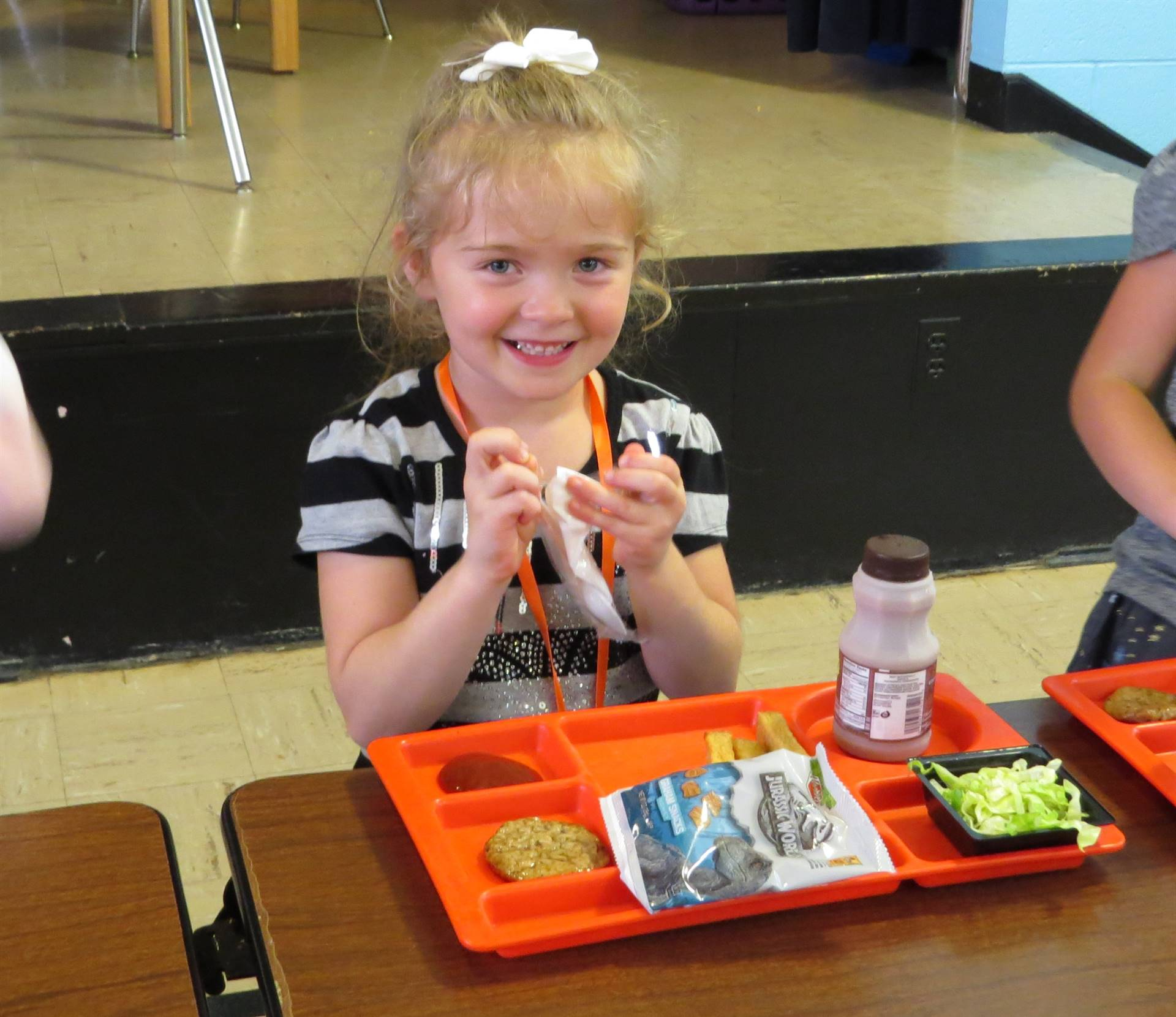 Female first grader eating lunch in cafeteria