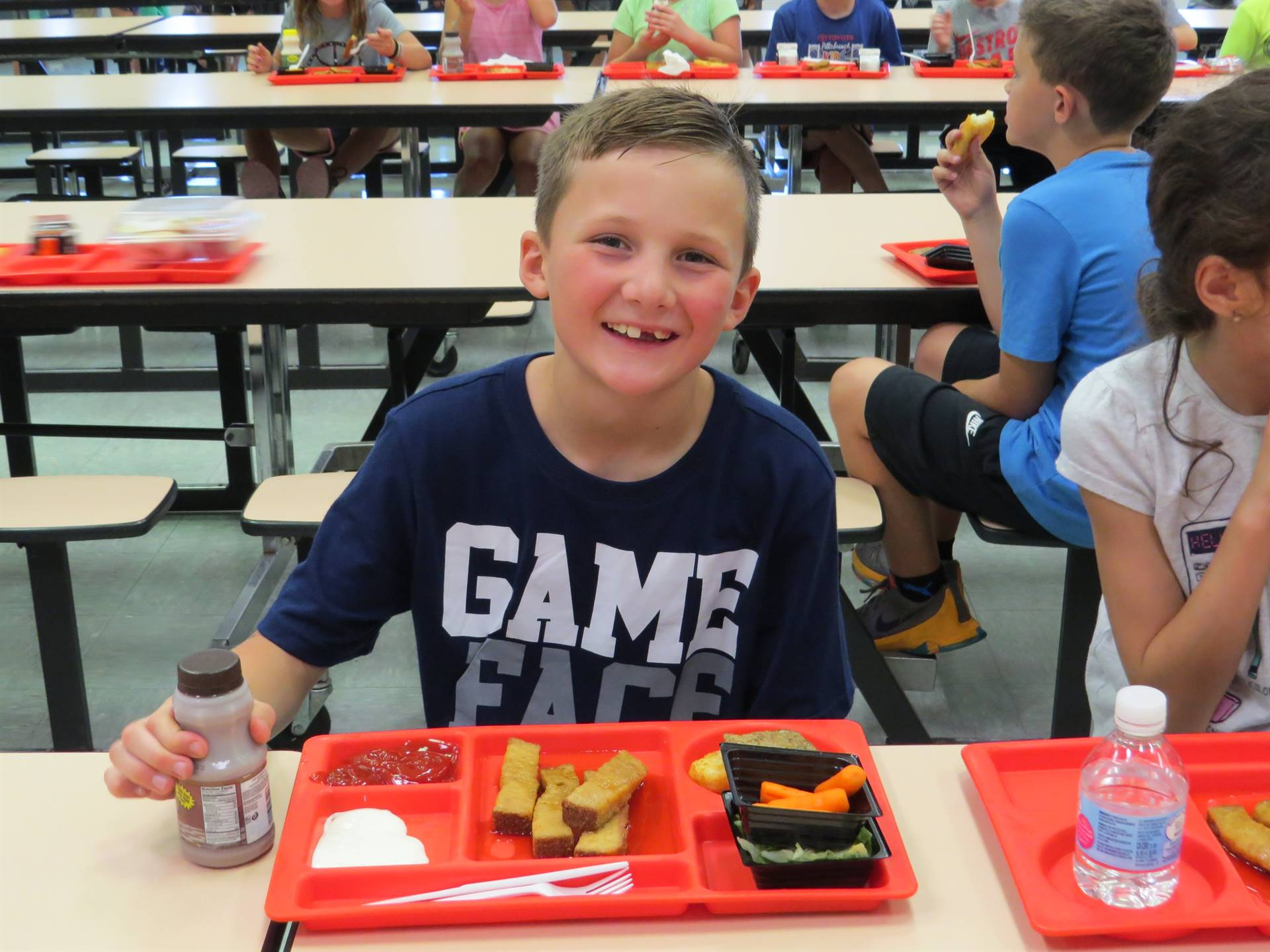 Male elementary student smiling with his lunch tray