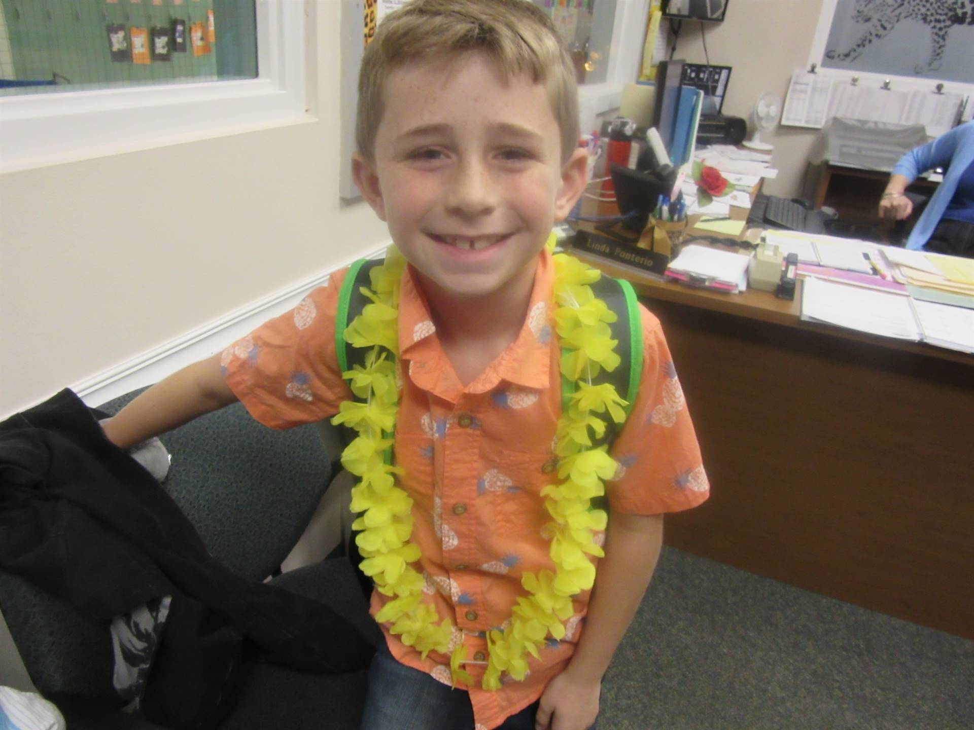 Student with flower leis on Hawaiian theme day