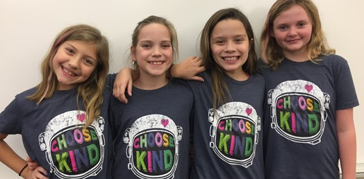 four girls posing with kindness shirts
