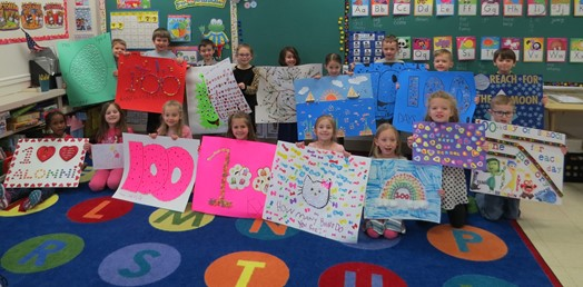 kindergarten students posed with 100 Day posters
