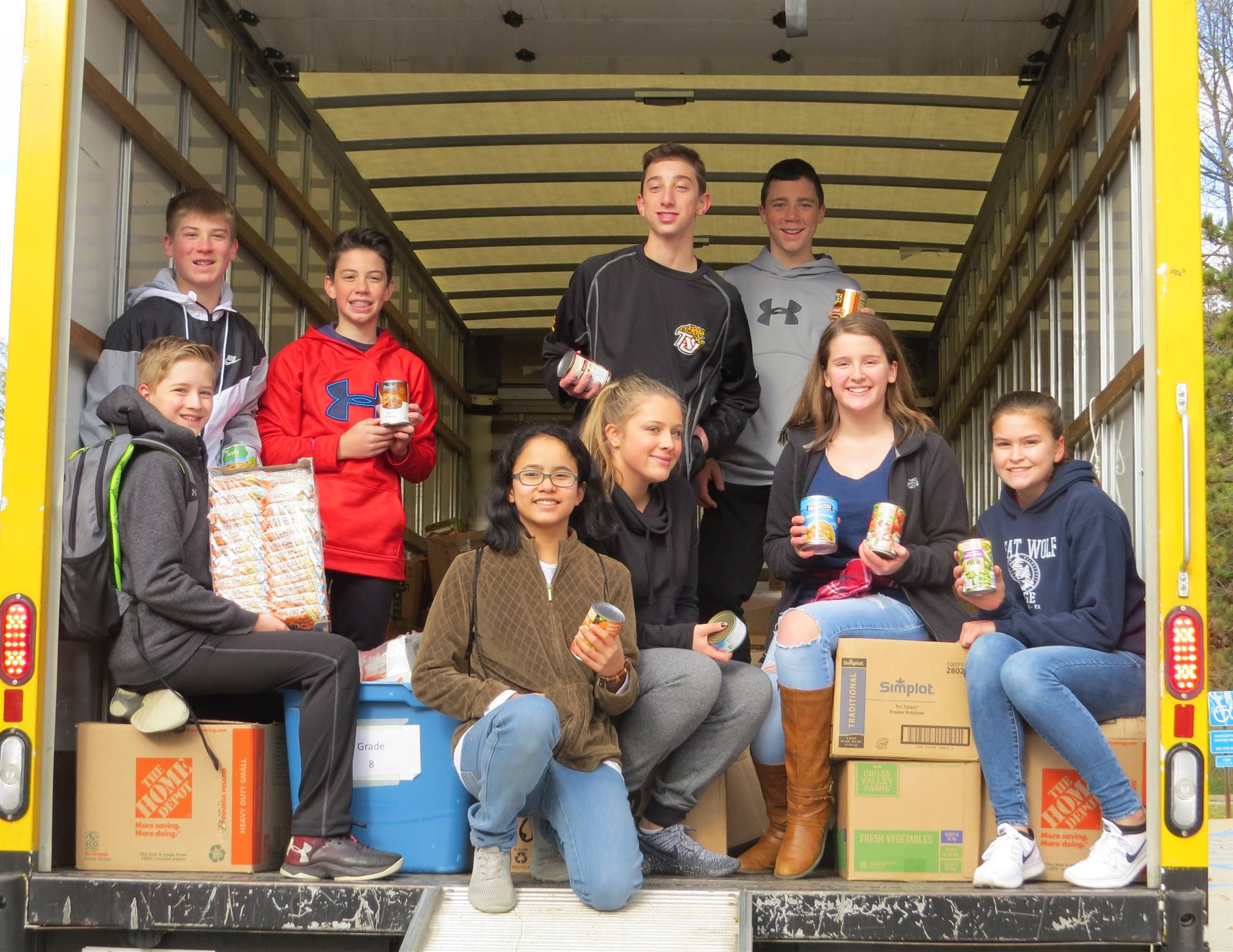 PHMS Students on back of truck delivering food to food bank