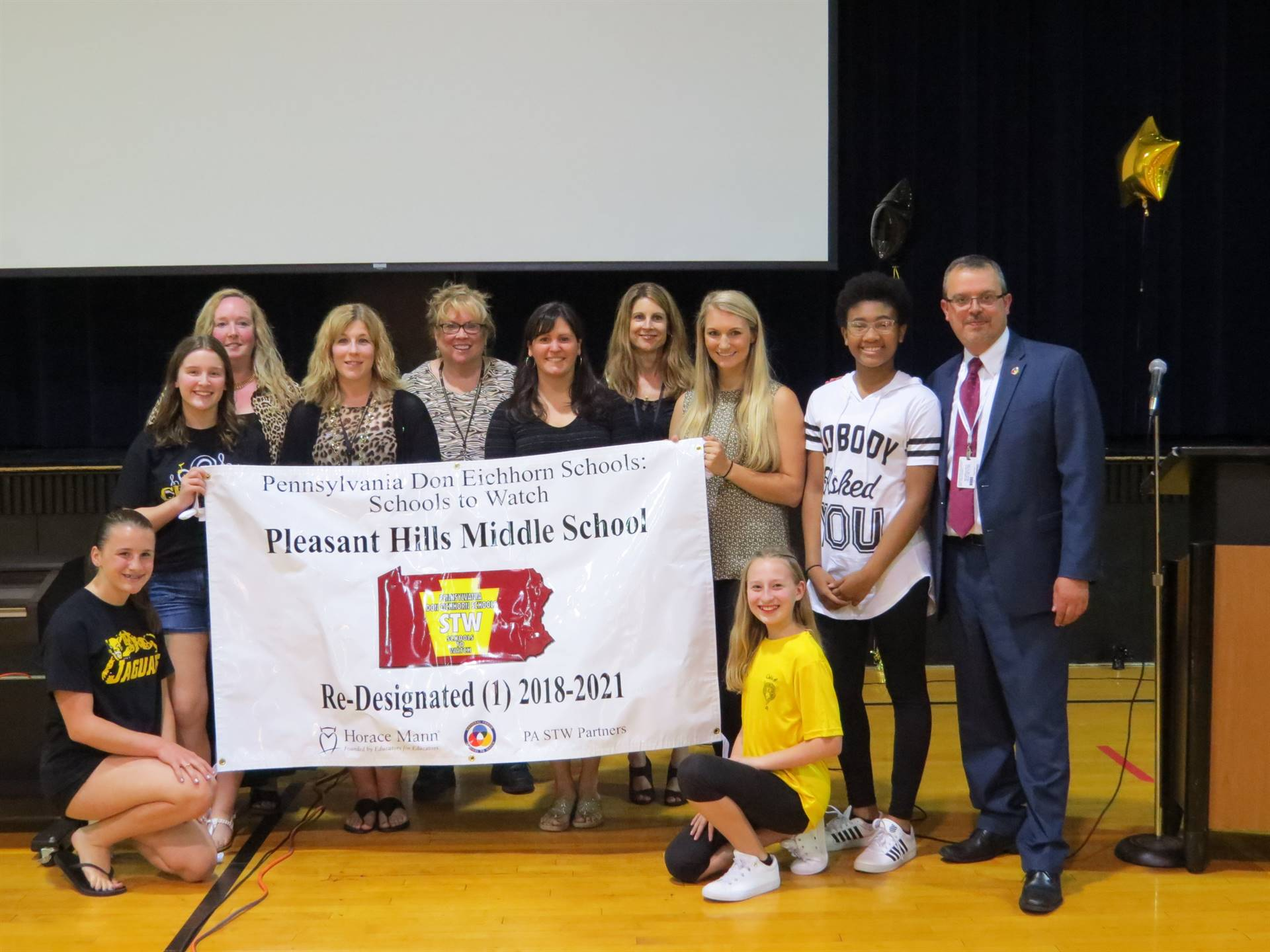 Students and Staff posed with Schools to Watch Banner