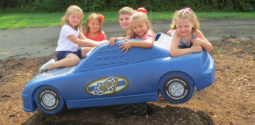 Kindergarten students riding a play car on the playground