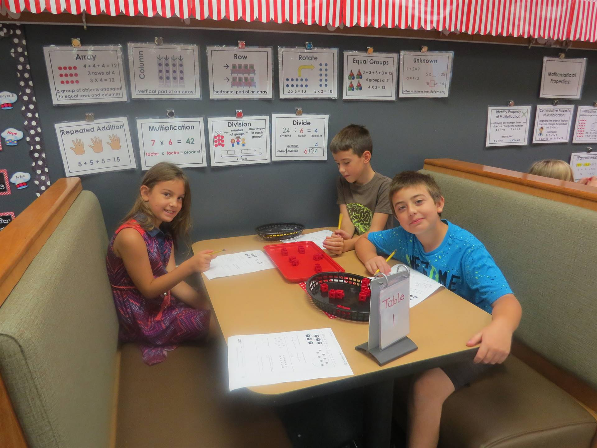 3rd graders sitting in classroom booth working on math papers