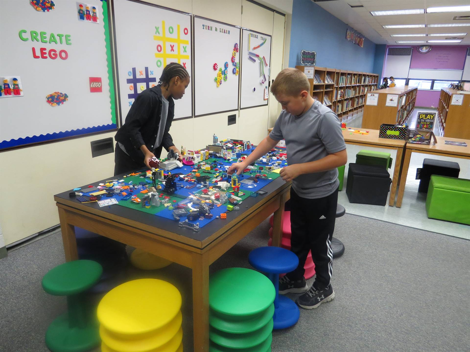 Male students creating Lego structures at the Lego Table
