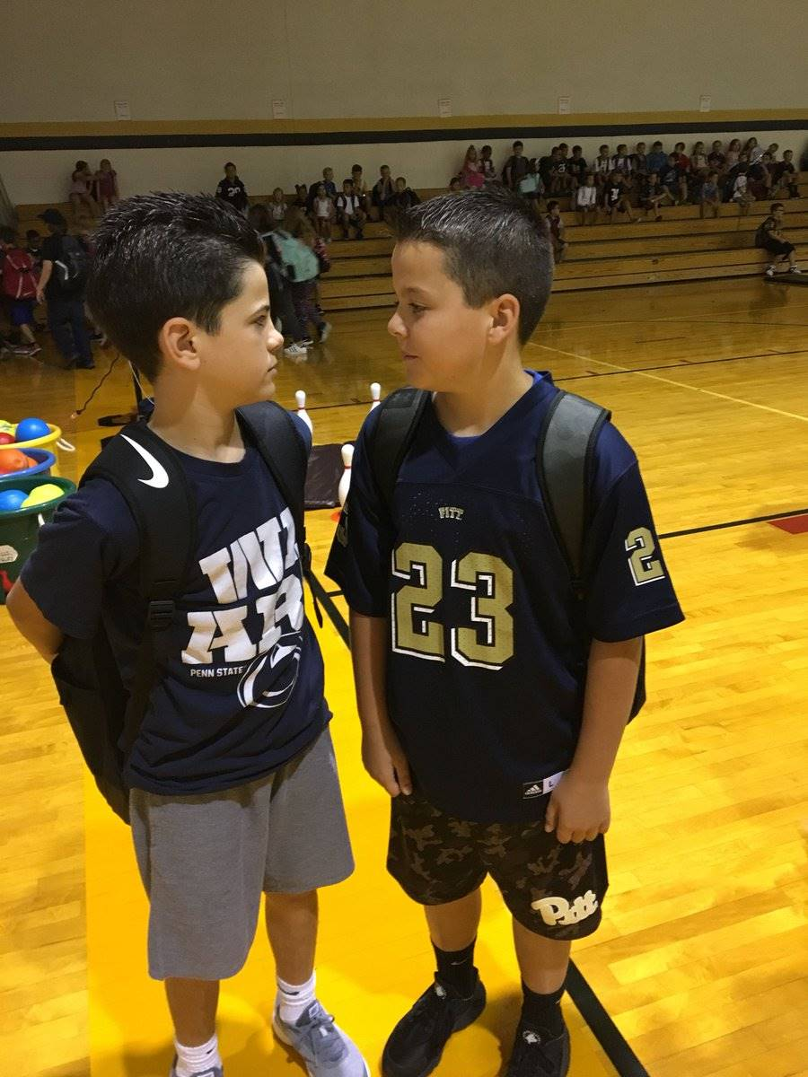 Male classmates with Pitt and Penn State football jerseys standing beside each other