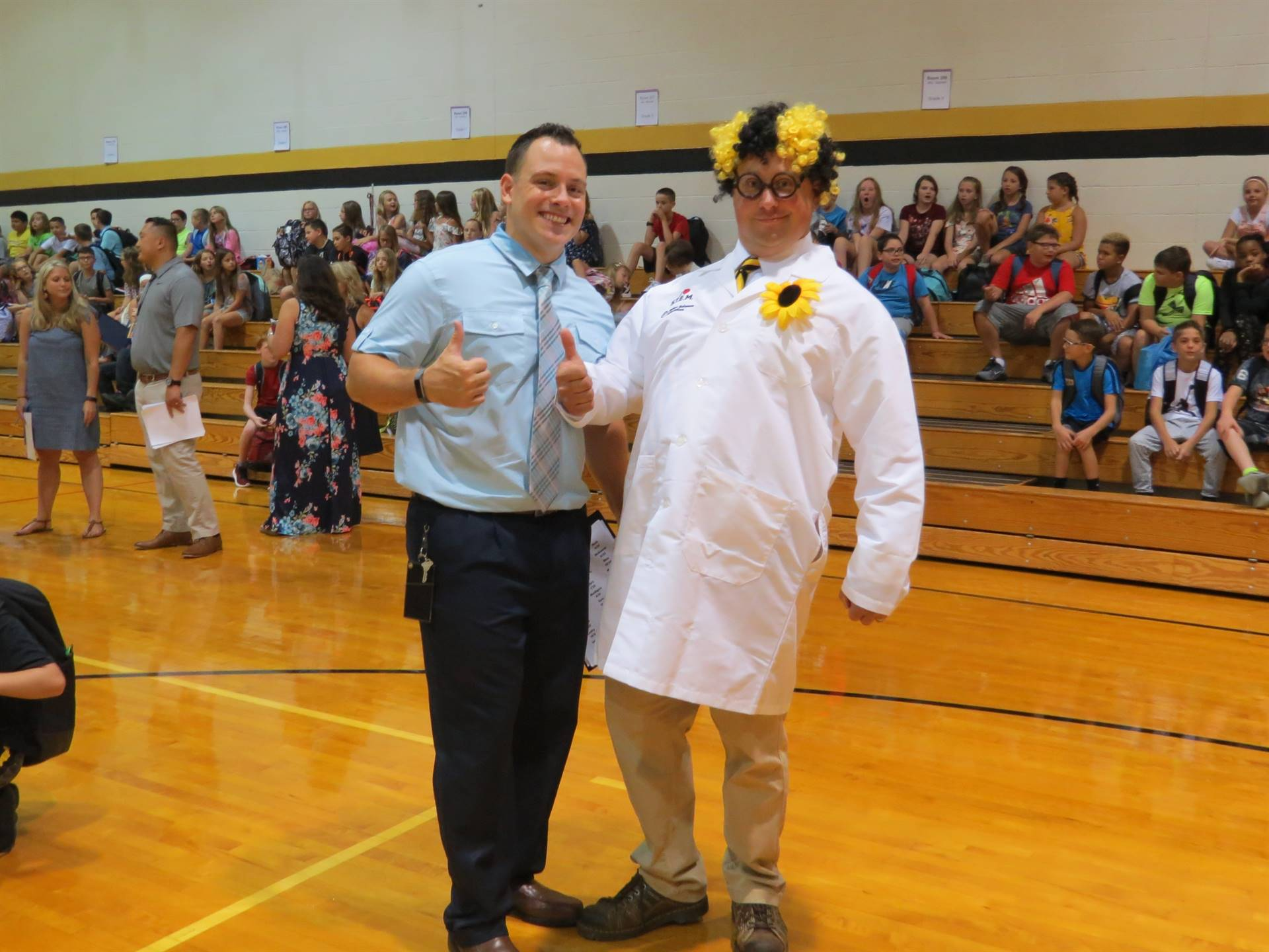 Mr. Chropka standing with Mr. Owen in his lab coat and black and gold wig