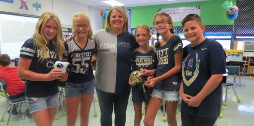 Students wearing Pitt and Penn State jerseys posing with their teacher