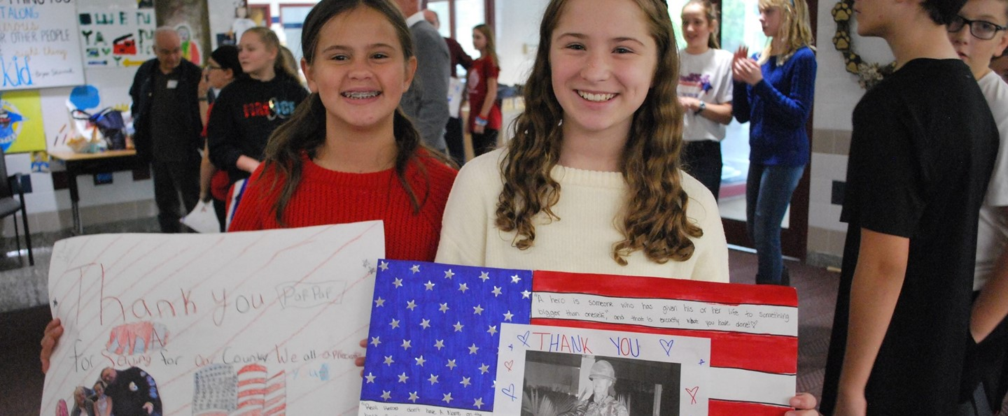 two girls holding thank you veterans signs