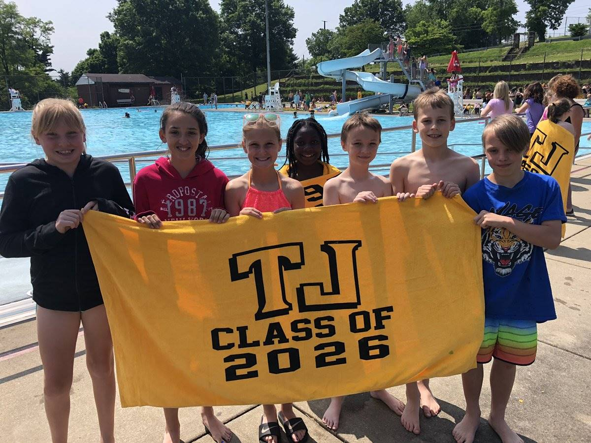 Students holding beach towel at pool