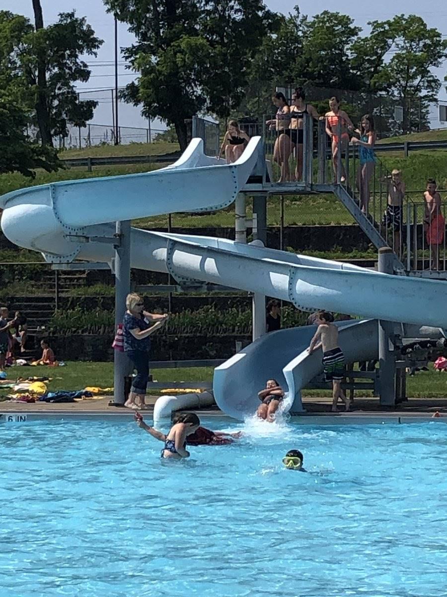Kids sliding down a pool slide