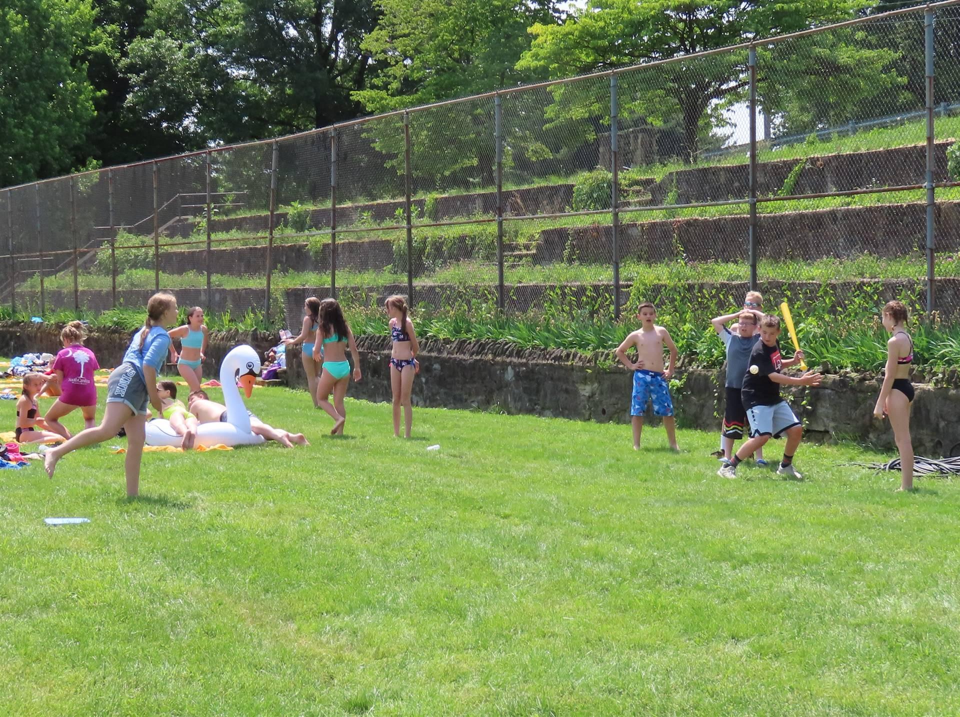Kids playing whiffle ball
