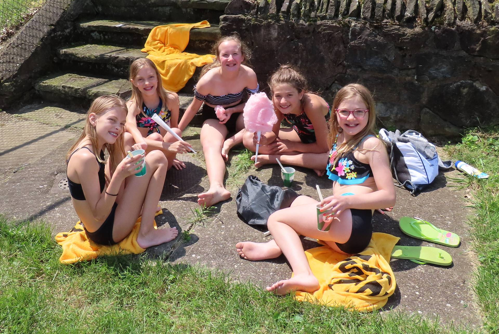 Girls enjoying snacks on beach towels
