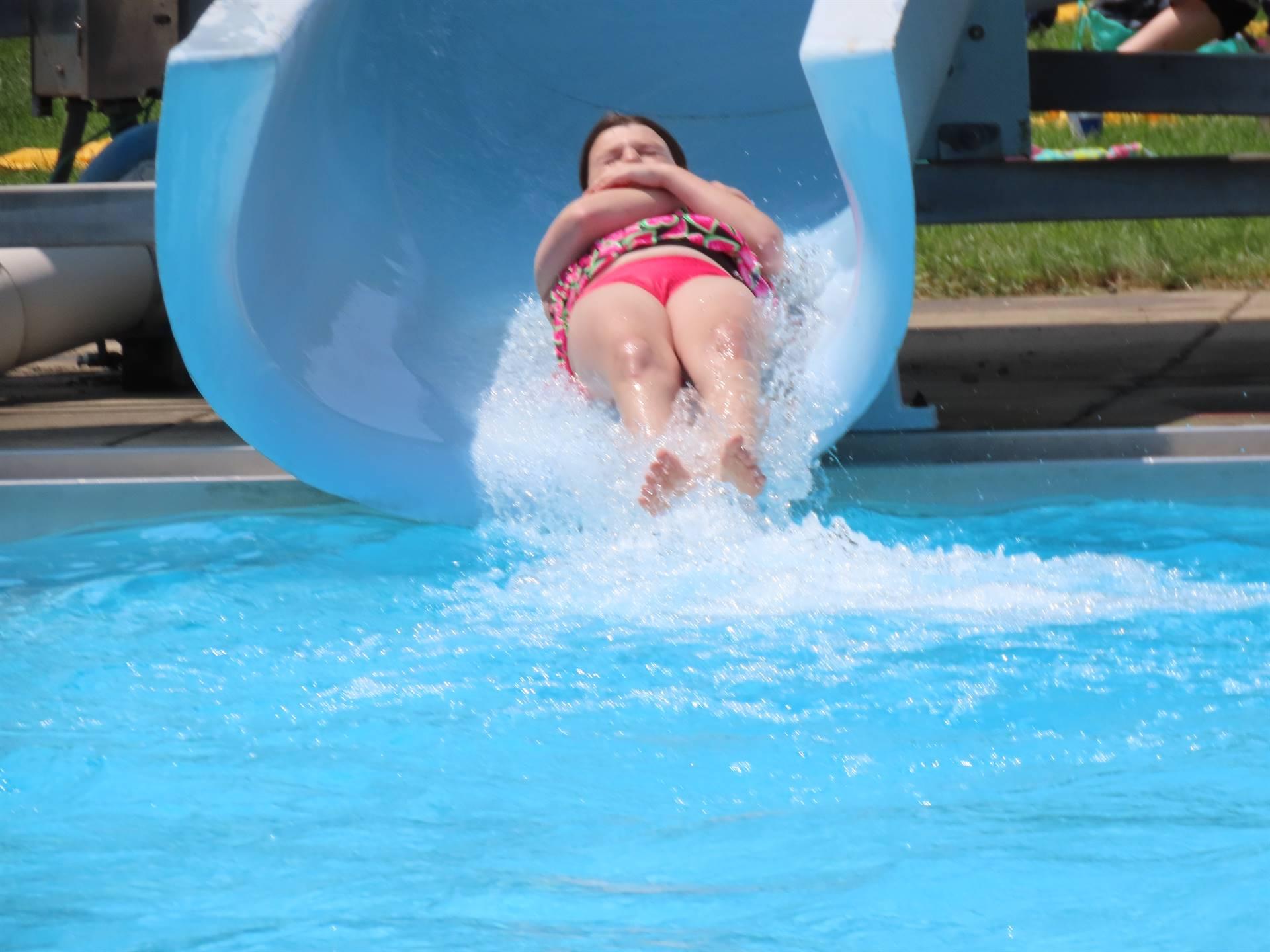Kids sliding down pool slide into water