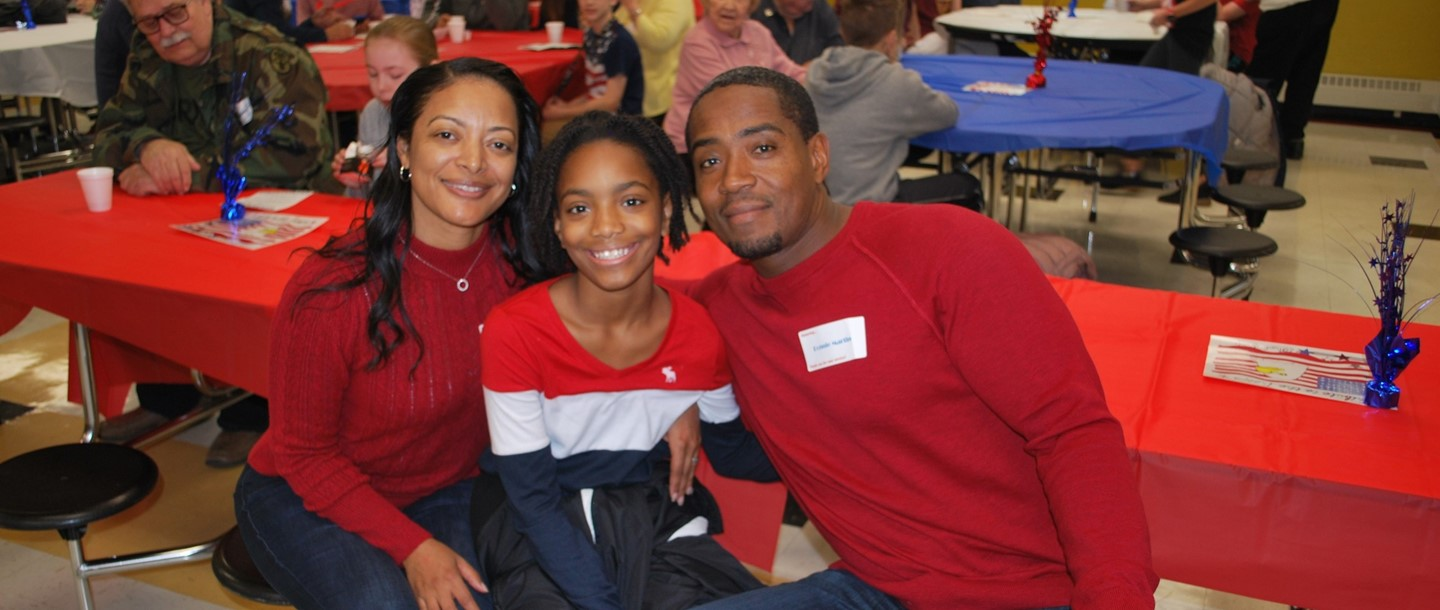 female student with parents at Veteran's Day breakfast