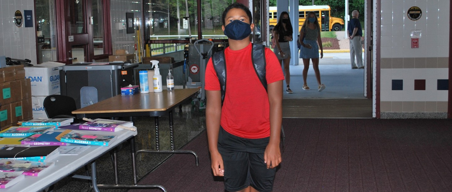 male student entering school wearing a mask