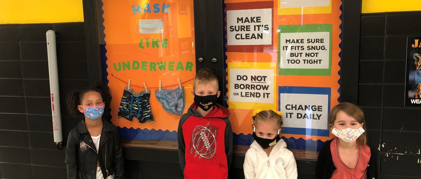 4 students wearing masks in the school lobby