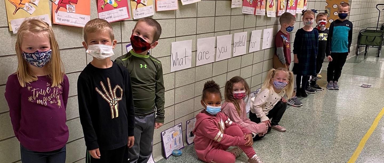 kindergarten students wearing masks waiting to enter classroom