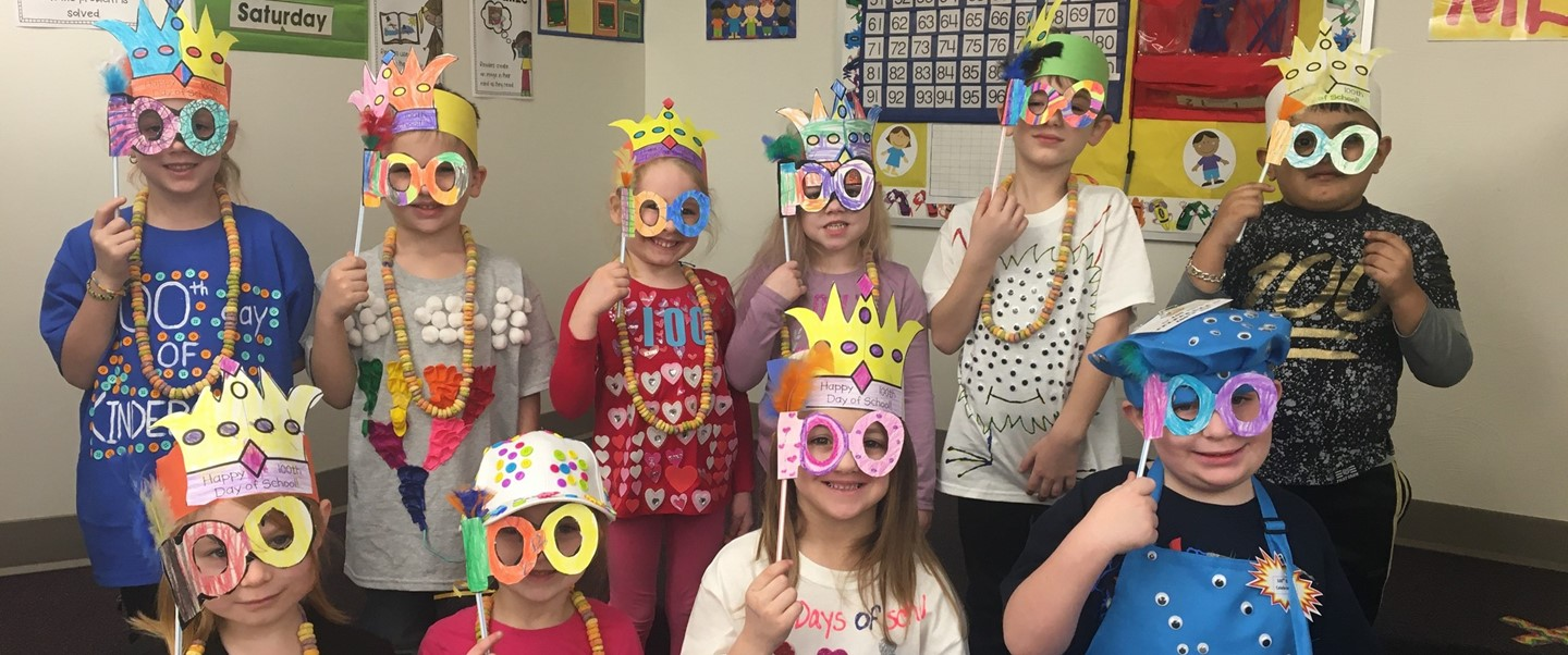 Kindergarten students holding 100 day masks to their face