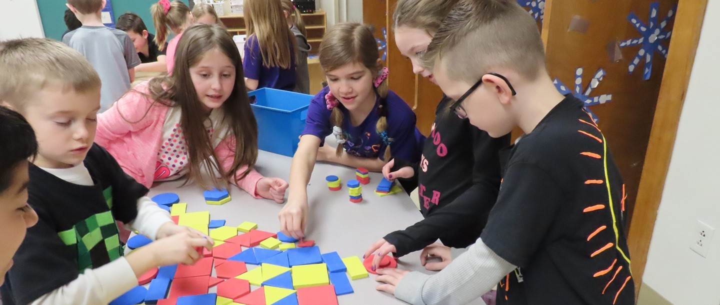 Table of First graders working on a math puzzle
