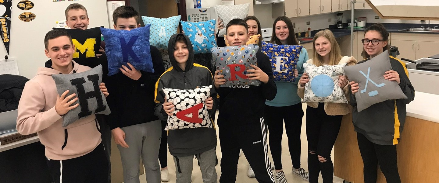 Students posing with their pillows they made in Family Consumer Science Class