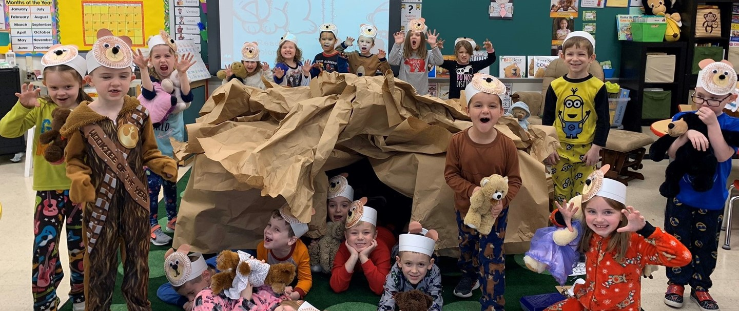 Students posing as bears in front of their bear cave