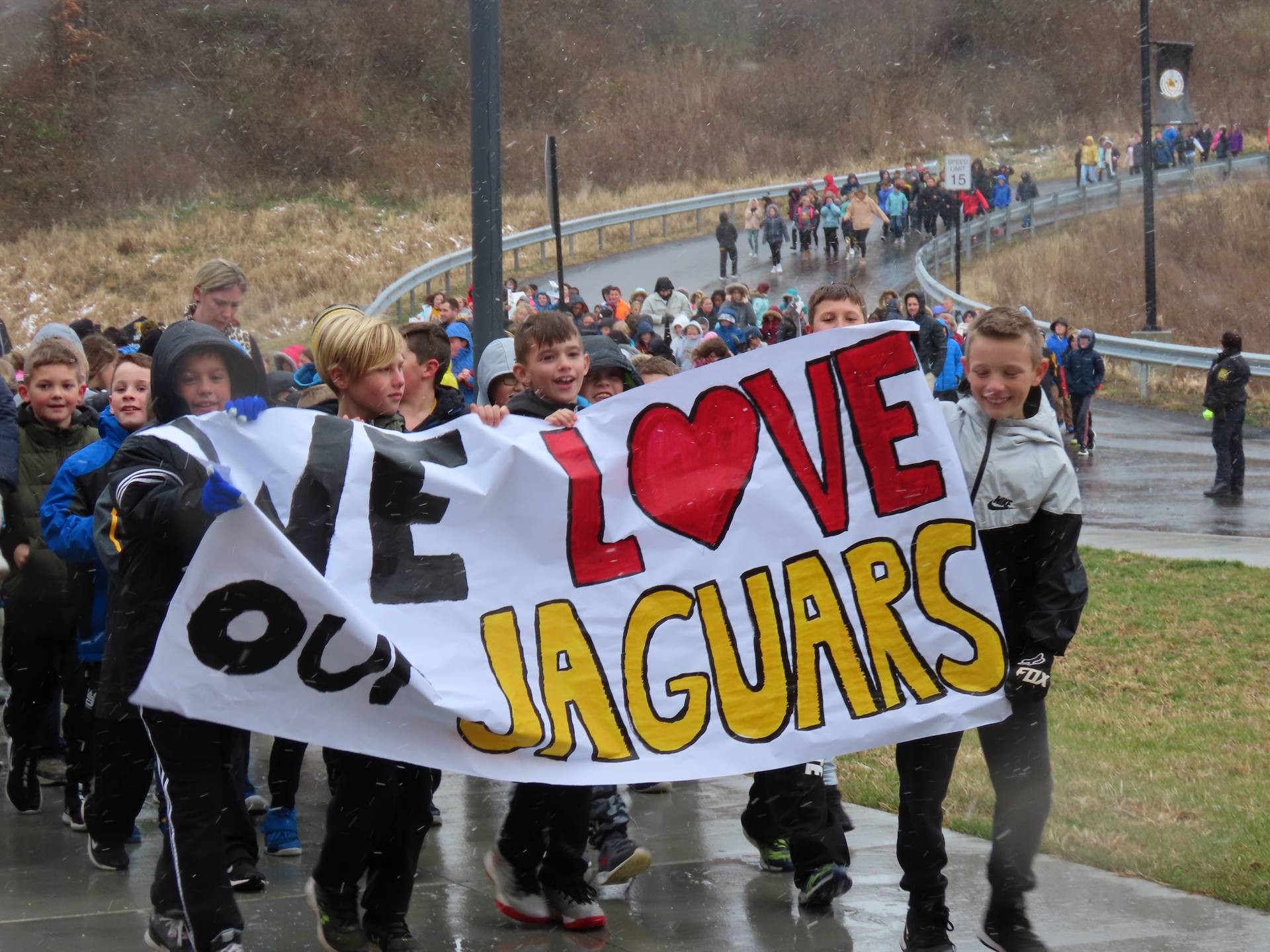 JHIS Students walking to TJHS with banner