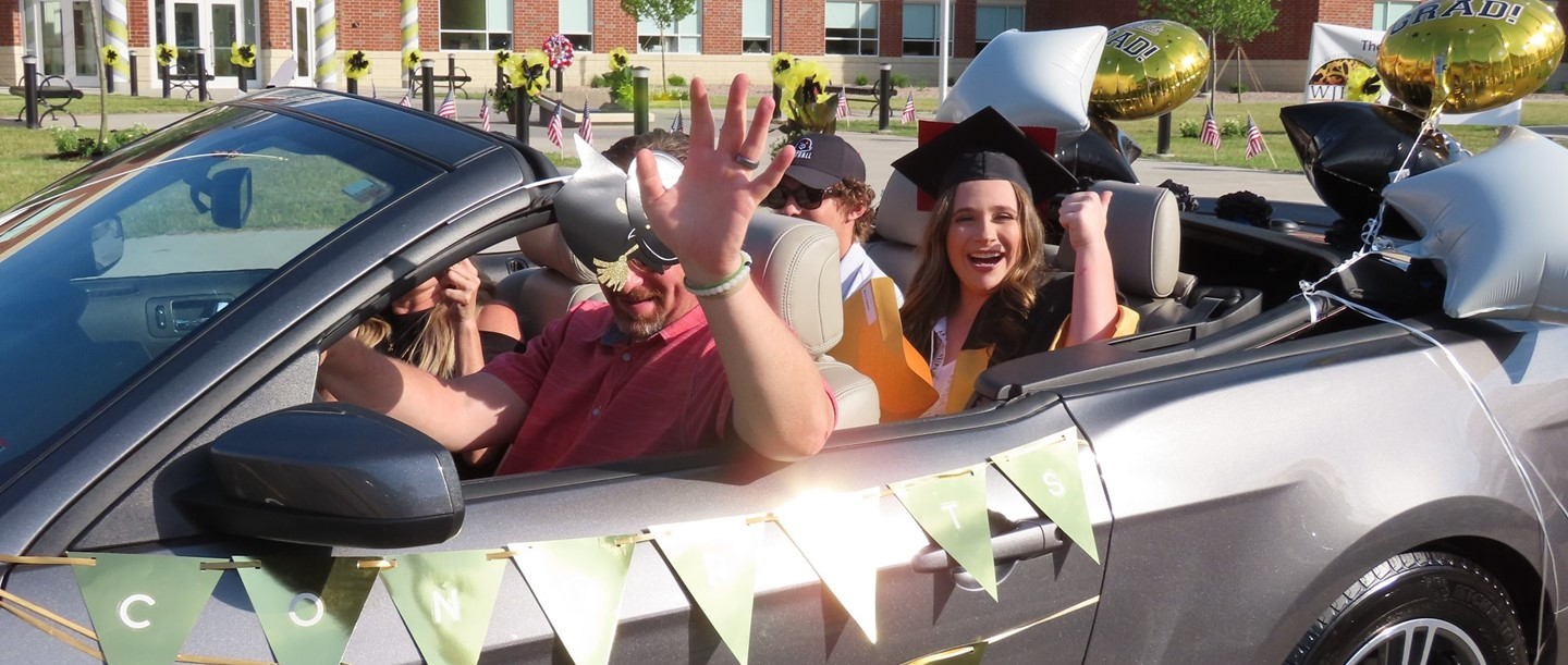 Graduate in the back of convertible waving