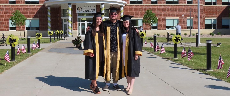 three graduates in front of high school