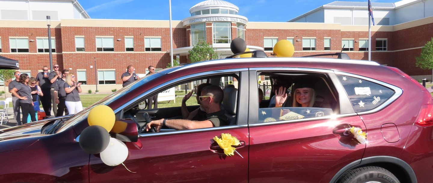 graduate waving from her car