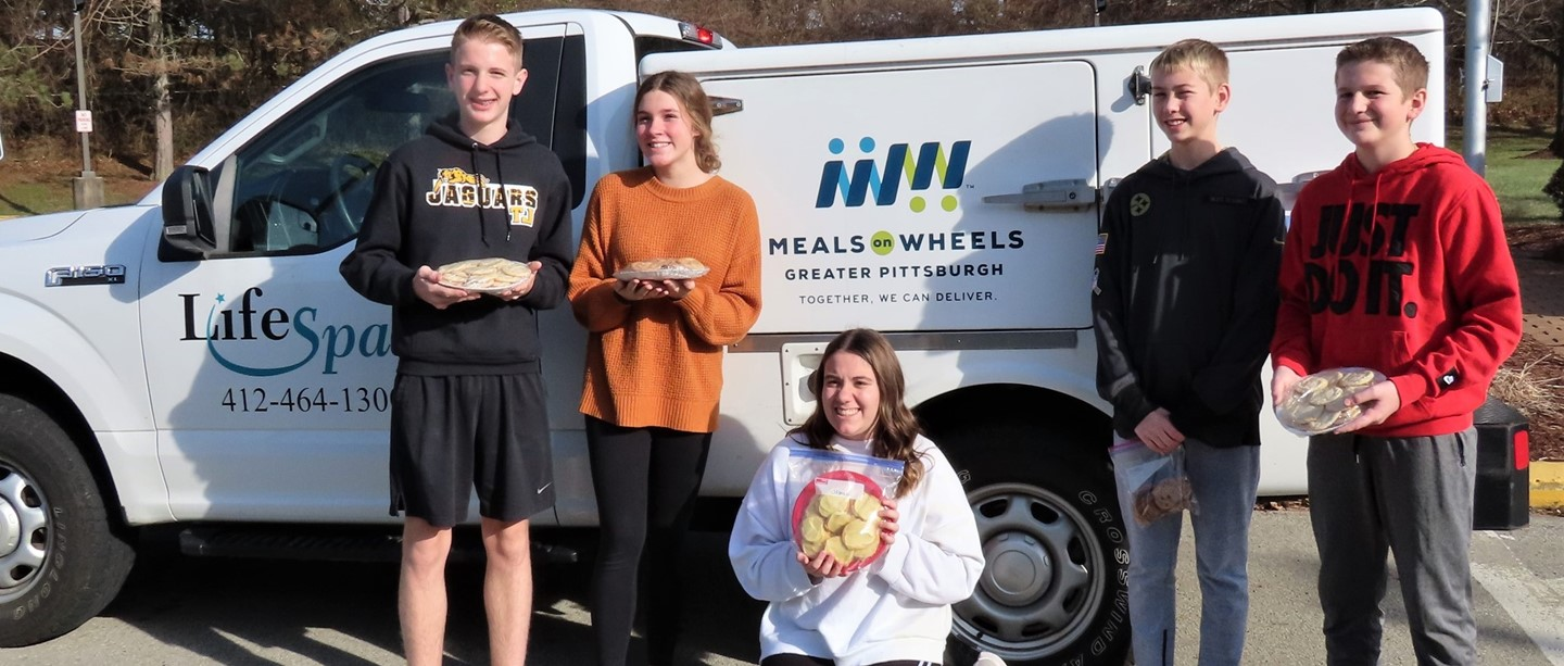 students posing with meals on wheels truck and cookie delivery