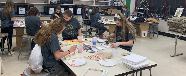 Girls painting in art class