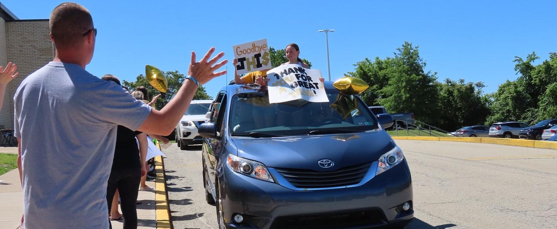 fifth grade girl waving goodbye to teacher in car parade
