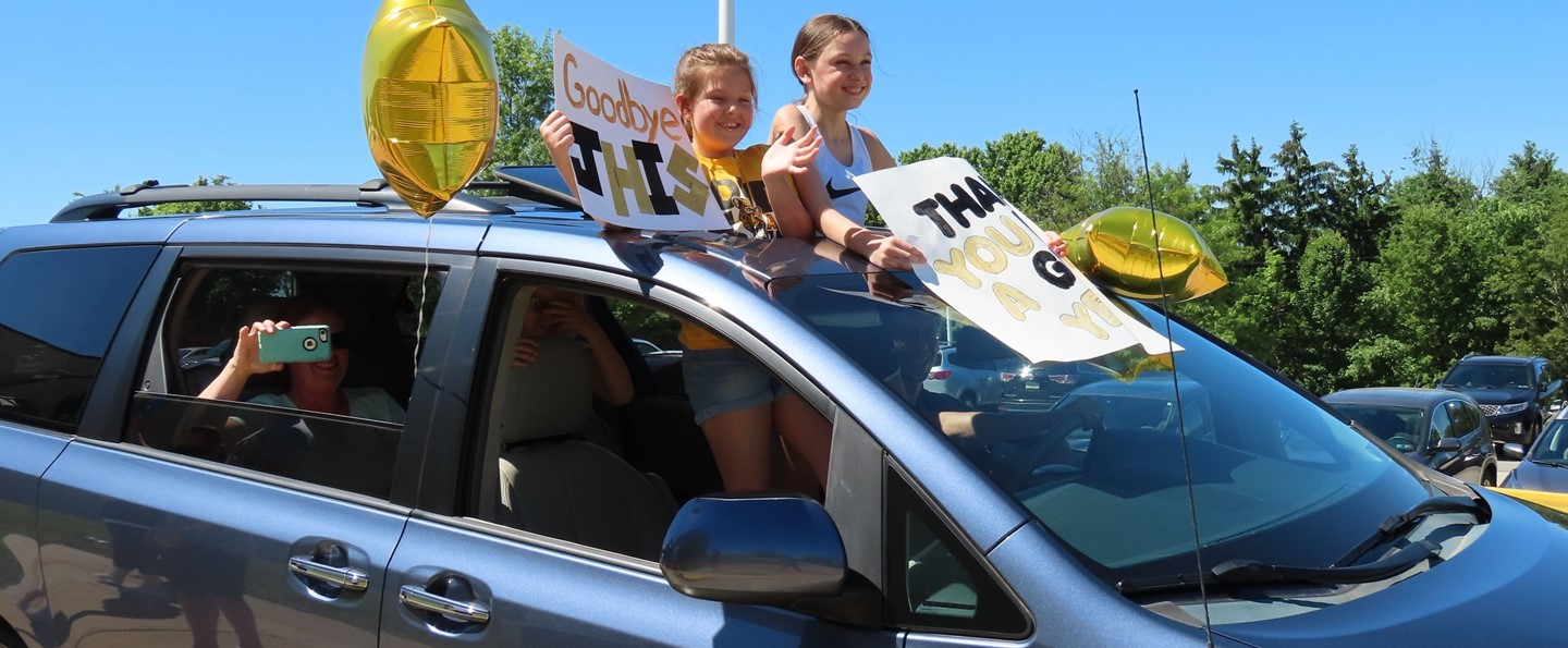 Fifth grade girls holding thank you signs in car parade