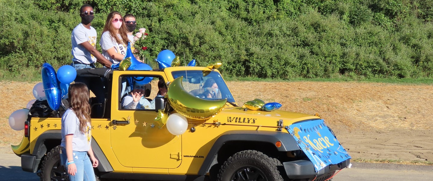 3 students riding in jeep for TJHS Homecoming parade
