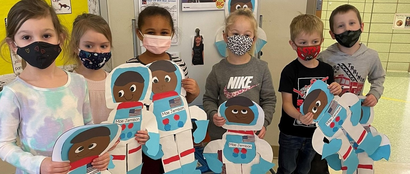 Students showing off their astronaut artwork